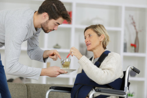 Caregiver giving cup of tea to disabled women in wheelchair