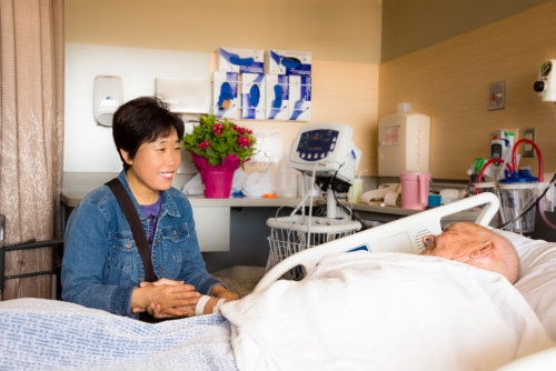 caregiver holding an elderly man's hand