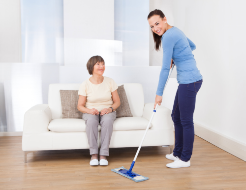 caregiver cleaning the floor with a mop while a senior woman sitting on the sofa